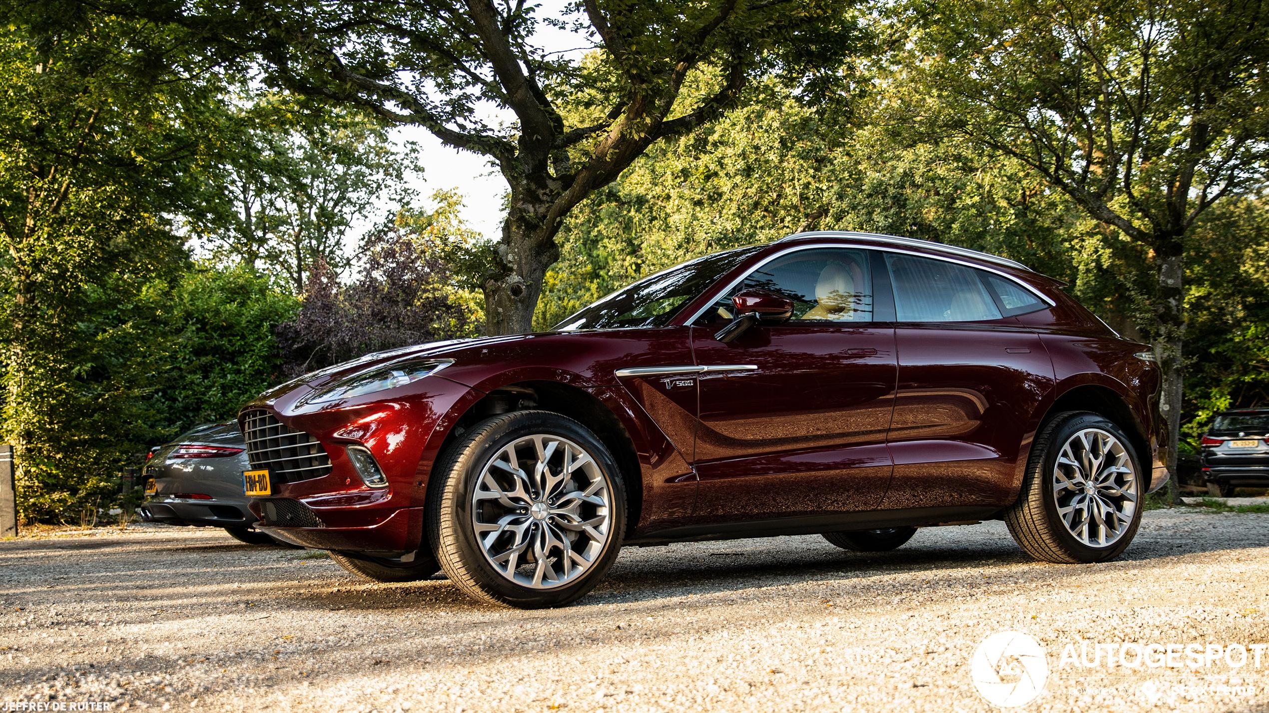 Donkerrode Aston Martin DBX kleurt wel in het avondzonnetje